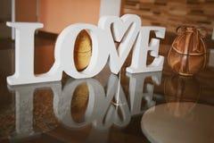 情人节和复活节概念与木信件爱,心形和两复活节彩蛋 免版税库存照片