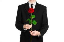 情人节和妇女的天题材:在拿着一朵红色玫瑰的衣服的人的手被隔绝在白色背景在演播室 免版税库存图片