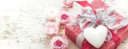 情人节和母亲节概念、红色礼物盒有弓的和玫瑰在轻的木背景 库存图片