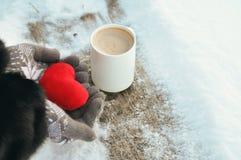 情人节和爱冷淡的图片:一在被编织的灰色手套的杯在一个长木凳的热的咖啡和手举行豪华的红色 免版税库存图片