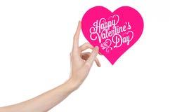 情人节和爱题材:手拿着一张贺卡以桃红色心脏的形式与词愉快的情人节 库存照片
