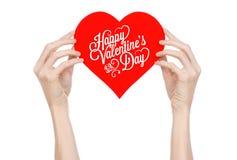 情人节和爱题材:手拿着一张贺卡以红色心脏的形式与词愉快的情人节 免版税库存照片