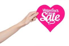 情人节和销售题目:递拿着卡片以在白色背景与词销售的桃红色心脏的形式隔绝的 免版税库存图片
