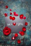 情人节在黑板的字法背景有红色心脏和玫瑰花瓣的,顶视图 免版税库存图片