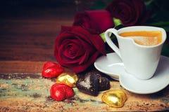 情人节庆祝用心脏巧克力、咖啡杯和玫瑰在木背景 图库摄影