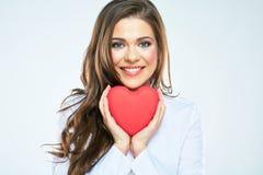 情人节微笑的妇女举行的红色心脏标志 免版税图库摄影