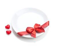 情人节心形的糖果和板材有红色弓的 免版税库存照片