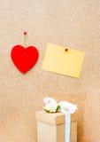 情人节心脏、礼物盒和黄色空的卡片在木 免版税库存图片