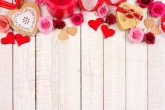 情人节心脏、花、礼物和装饰上面边界在白色木头 免版税库存图片