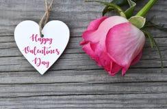 情人节快乐与桃红色玫瑰的贺卡和与文本的装饰白色心脏在老木背景 2月14日 图库摄影