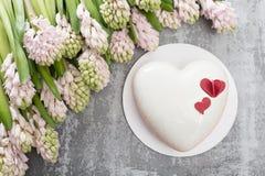 情人节或生日贺卡 以白色心脏的形式蛋糕 桃红色风信花和点心在葡萄酒 免版税库存照片