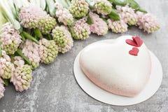 情人节或生日贺卡 以白色心脏的形式蛋糕 桃红色风信花和点心在葡萄酒 免版税图库摄影