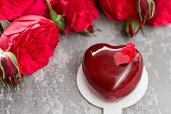 情人节或生日贺卡 以红色心脏的形式蛋糕 英国兰开斯特家族族徽和点心在葡萄酒木桌上 库存图片