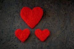 情人节手工制造一大和两小心脏的贺卡从毛毡白色和红颜色 免版税库存图片