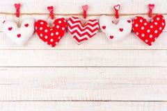 情人节手工制造布料心脏在白色木头的一条线把枕在 免版税库存图片