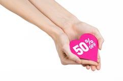 情人节打折题目:递拿着卡片以与折扣的桃红色心脏的形式50%在被隔绝 免版税库存图片