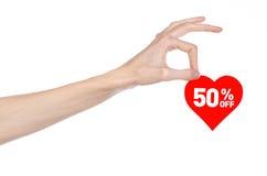 情人节打折题目:递拿着卡片以与折扣的红色心脏的形式50%在被隔绝 免版税库存图片