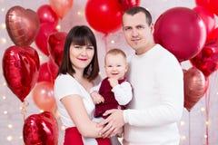 情人节概念-与女儿的年轻家庭在红色心形的气球背景 免版税库存图片