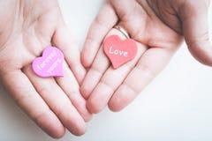情人节概念 与爱题字的红色装饰心脏和与永远题字的紫心勋章你的在女性手上 免版税图库摄影