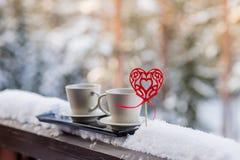 情人节概念-两杯茶,咖啡,在雪背景前面的热的饮料 两个杯子用在的热的咖啡 免版税库存照片