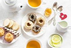 情人节浪漫早餐柠檬绿茶和甜点-香蕉松饼、曲奇饼用焦糖和坚果,油炸圈饼与chocol 库存图片