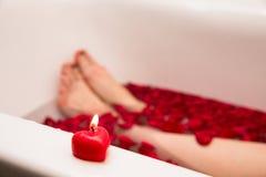 情人节浪漫浴,家庭温泉,与玫瑰色petails的浴,红色听见蜡烛,自已关心 免版税库存图片