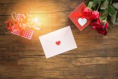 情人节礼物盒红色和桃红色在木背景/情人节卡片红色玫瑰色花和礼物盒 免版税库存照片