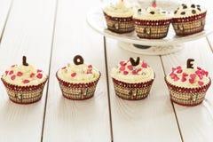 情人节红色天鹅绒杯形蛋糕与在轻的白色木背景,水平的看法洒 图库摄影