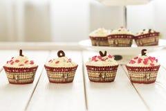 情人节红色天鹅绒杯形蛋糕与在轻的白色木背景,水平的看法洒 免版税库存图片