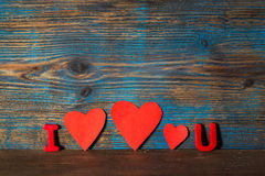情人节背景,磁铁在i上写字和u和三红色心脏之间在木背景 免版税图库摄影