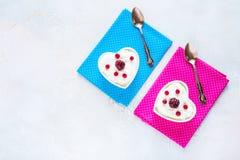 情人节装饰,早餐,酸奶用两的莓果在桌上的白色心形的碗 顶视图,平的位置 图库摄影
