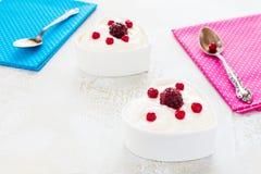 情人节装饰,早餐,酸奶用两的莓果在桌上的白色心形的碗 免版税库存照片