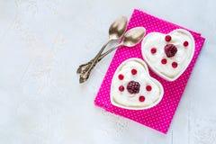 情人节装饰,早餐,酸奶用两的莓果在桌上的白色心形的碗 免版税图库摄影