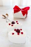 情人节装饰,早餐,酸奶用两的莓果在桌上的白色心形的碗 库存照片
