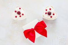 情人节装饰,早餐,酸奶用两的莓果在白色心形的碗和礼物盒在桌上 库存照片