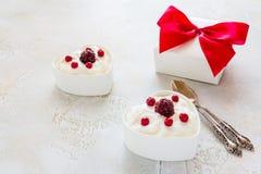 情人节装饰,早餐,酸奶用两的莓果在白色心形的碗和礼物盒在桌上 库存图片