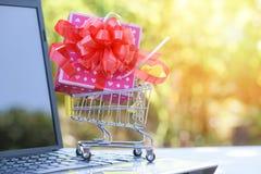 情人节购物和礼物盒桃红色当前箱子有红色丝带弓的在在网上购物的手推车 免版税库存照片