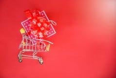 情人节购物和礼物盒桃红色当前箱子有红色丝带弓的手推车概念愉快圣诞快乐的假日 免版税库存图片