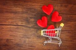 情人节购物和红心在手推车爱概念/购物的假日爱的 库存图片