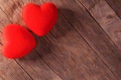 情人节,在木地板上的红色天鹅绒心脏 免版税库存图片