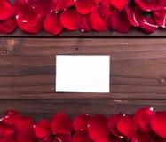 情人节:白色空的纸牌和玫瑰花瓣 库存图片