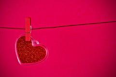 情人节系列,垂悬在红色背景的装饰红色心脏 免版税库存图片