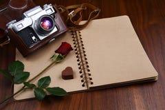 情人节-罗斯、在笔记本的巧克力和照相机 免版税图库摄影