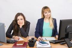 情况在办公室-坐在失望的一张桌,其他上的妇女愉快地看屏幕 库存照片