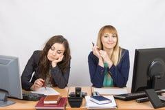 情况在办公室-看本文的妇女翻倒,其他愉快地调查框架 库存照片