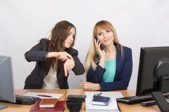 情况在办公室-雇员显示长期观看那个同事谈在电话 免版税库存图片