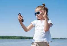 情感、表示和人概念-采取与智能手机的愉快的小孩子或十几岁的女孩selfie在天空蔚蓝 免版税库存照片