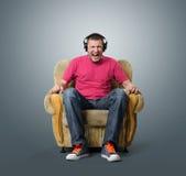 情感人听到在耳机的音乐 免版税库存图片