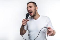 情感人唱在话筒的歌曲并且晃动  他享用做那 背景查出的白色 免版税库存照片