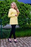 情感地摆在公园的黄色外套的可爱的金发碧眼的女人 库存图片